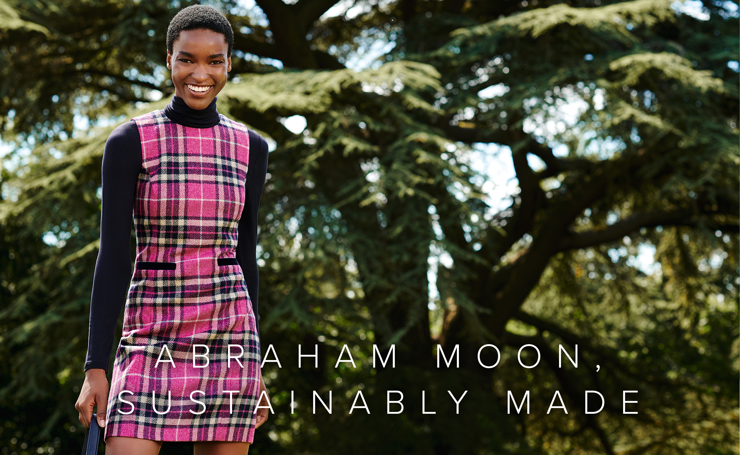 Alt text: Hobbs wool shift dress with a check pattern in pink shades made from Abraham Moon's British made sustainable wool fabric, layered over a navy blue turtleneck women's jumper styled with a leather tote bag.