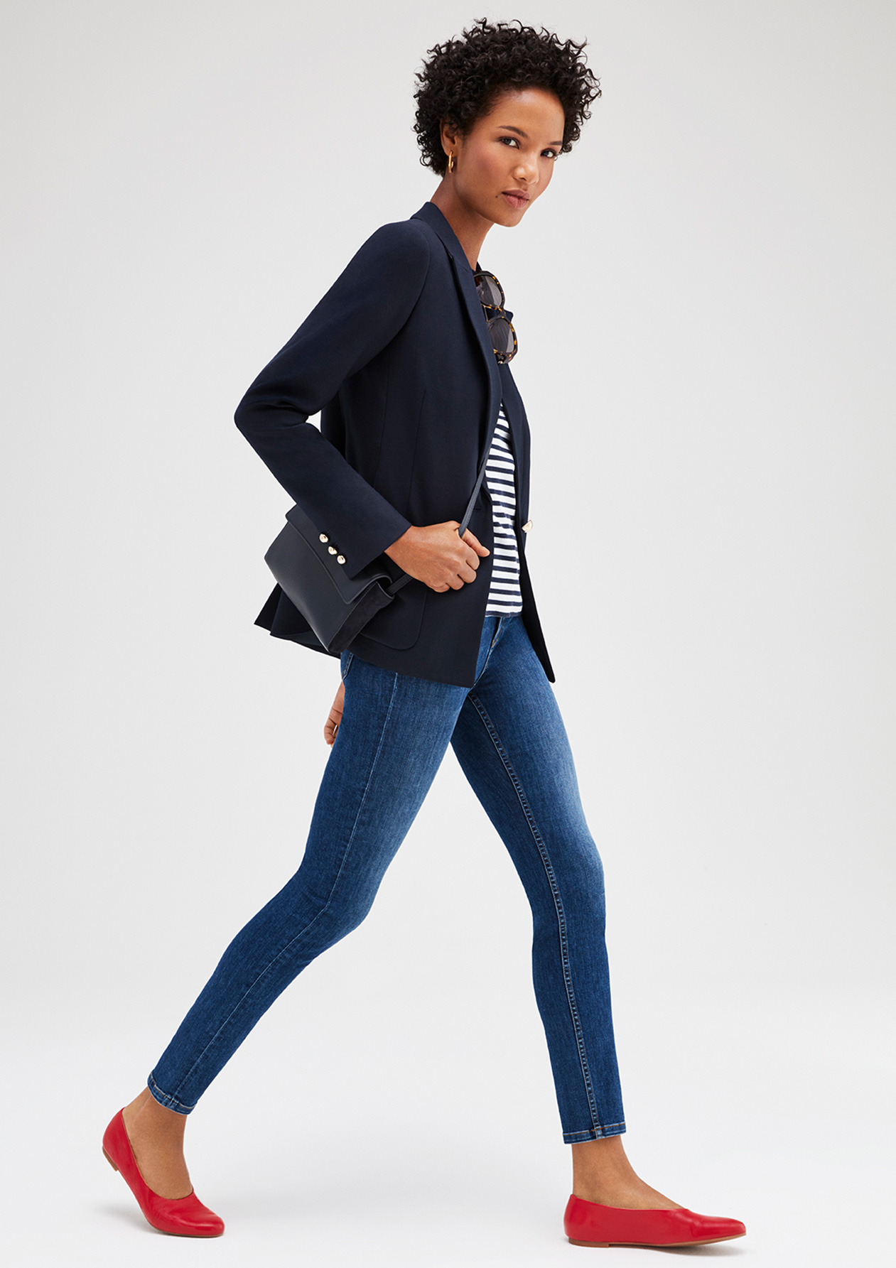 Nail relaxed style, model wears a casual outfit consisting of a classic navy blazer, striped top, blue jeans and red flats.