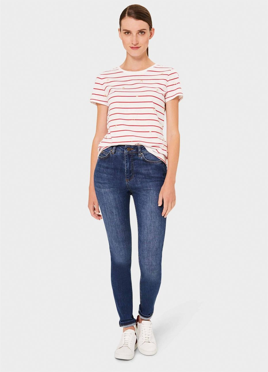 White tshirt with red stripes styled with blue denim jeans and white trainers by Hobbs.