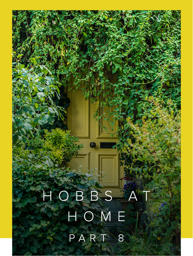 A yellow front door surronded by greenery