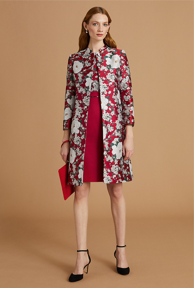 Model wears a red jacquard floral shift dress and coat co-ord, Mary-Jane heels and a clutch bag.