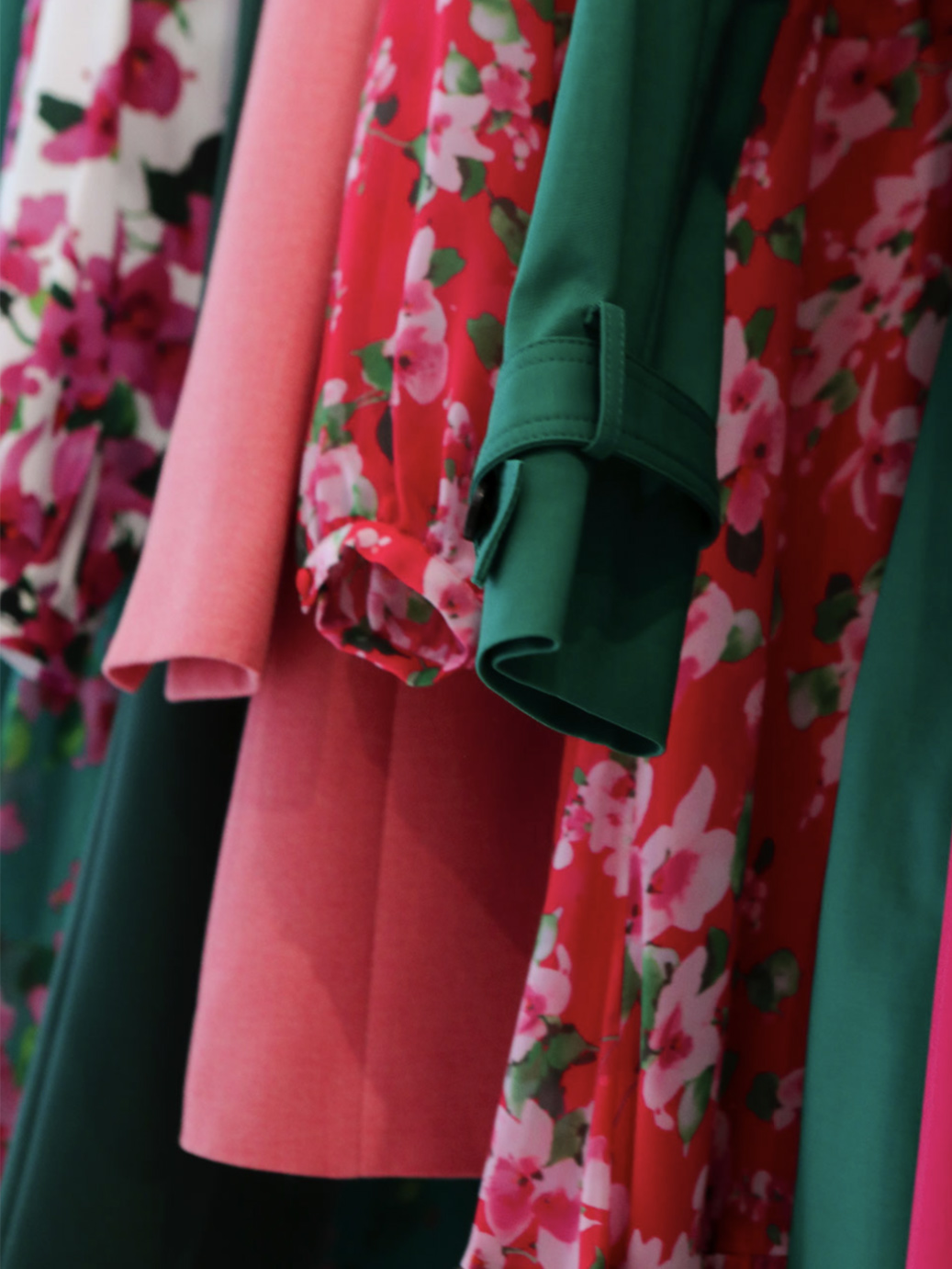 BlInterior image of wardobe featuring bright pink, green and floral clothing