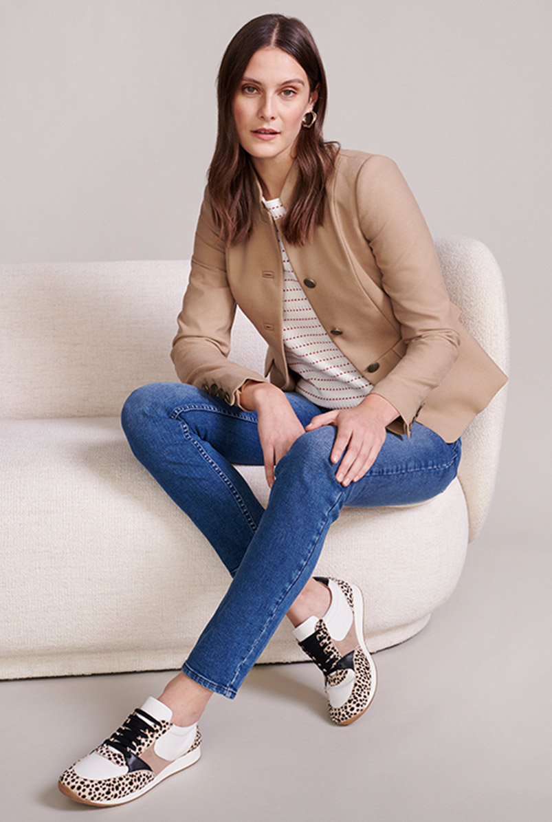 Model sits on a cream sofa wearing a military style jacket, jeans and leopard trainers.