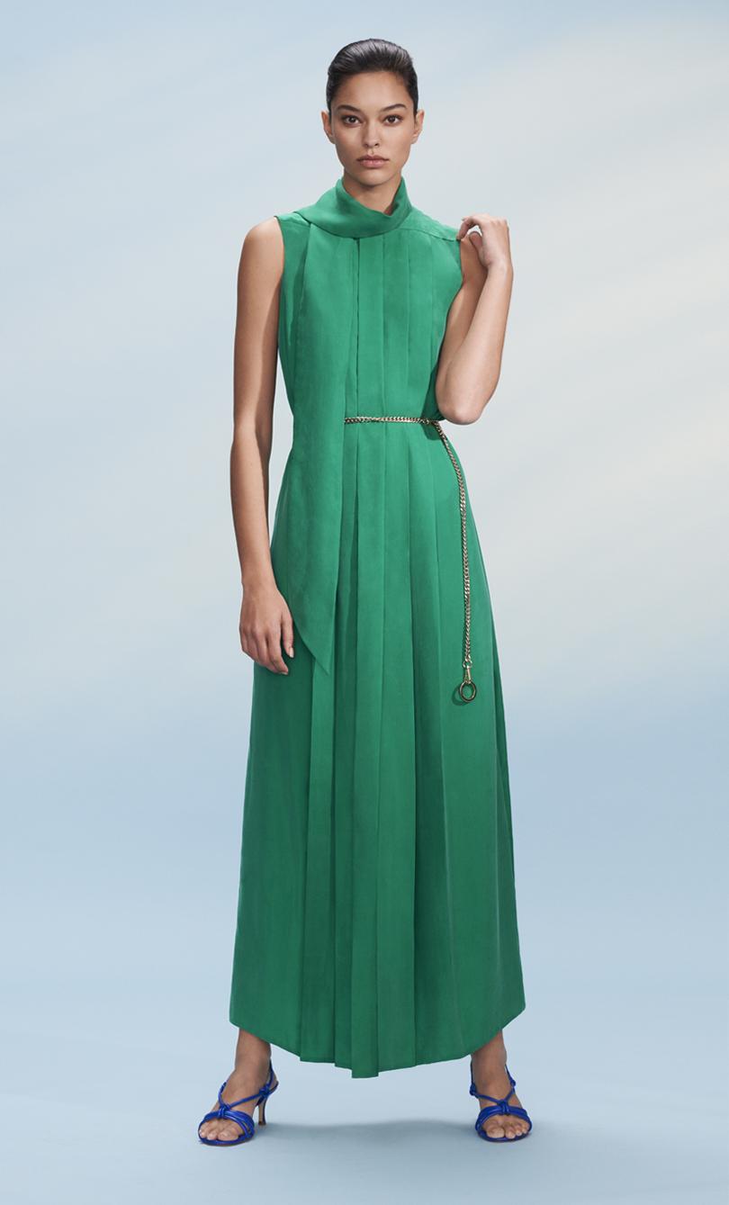 Model posing in a paradise green long dress
