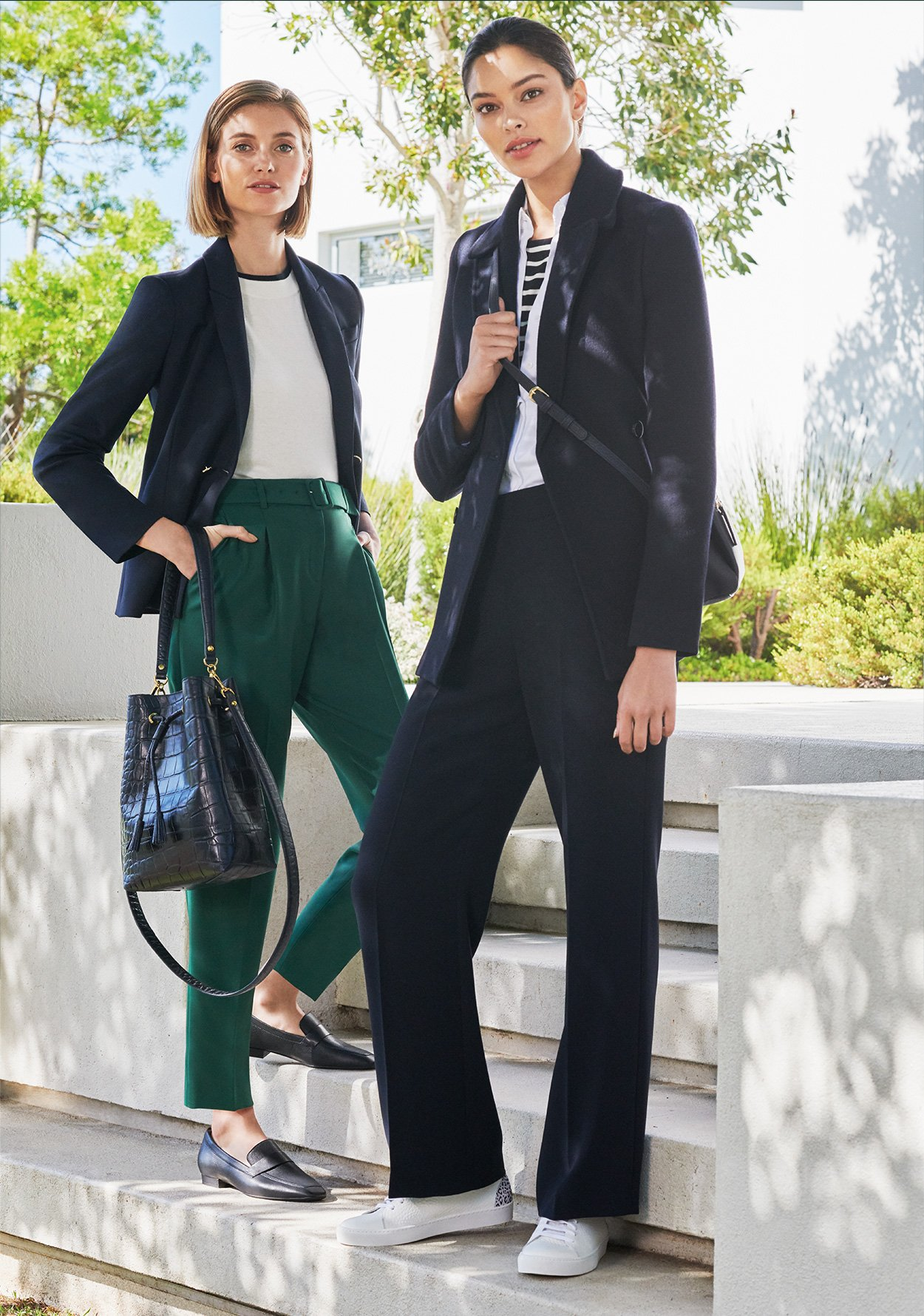 Two women pose in a garden. One wears a navy tailored jacket, striped top and green tapered trouser with loafers and leaher loafers. The  other wears a navy blazer with navy wide leg trousers styled with white trainers and a navy blue cross body bag.