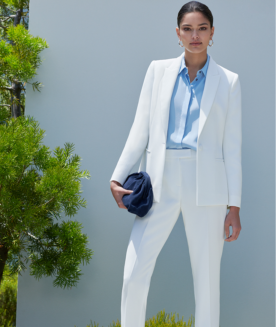 Women's trouser suit in white worn with light blue shirt and dark navy clutch by Hobbs.