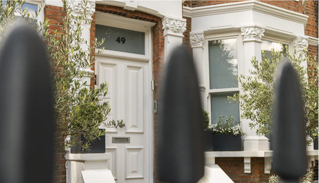 The front of an Edwardian red brick London home with a white front door