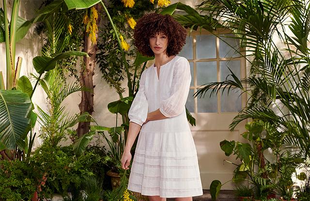Model wearing a Hobbs cream summer dress in a conservatory.
