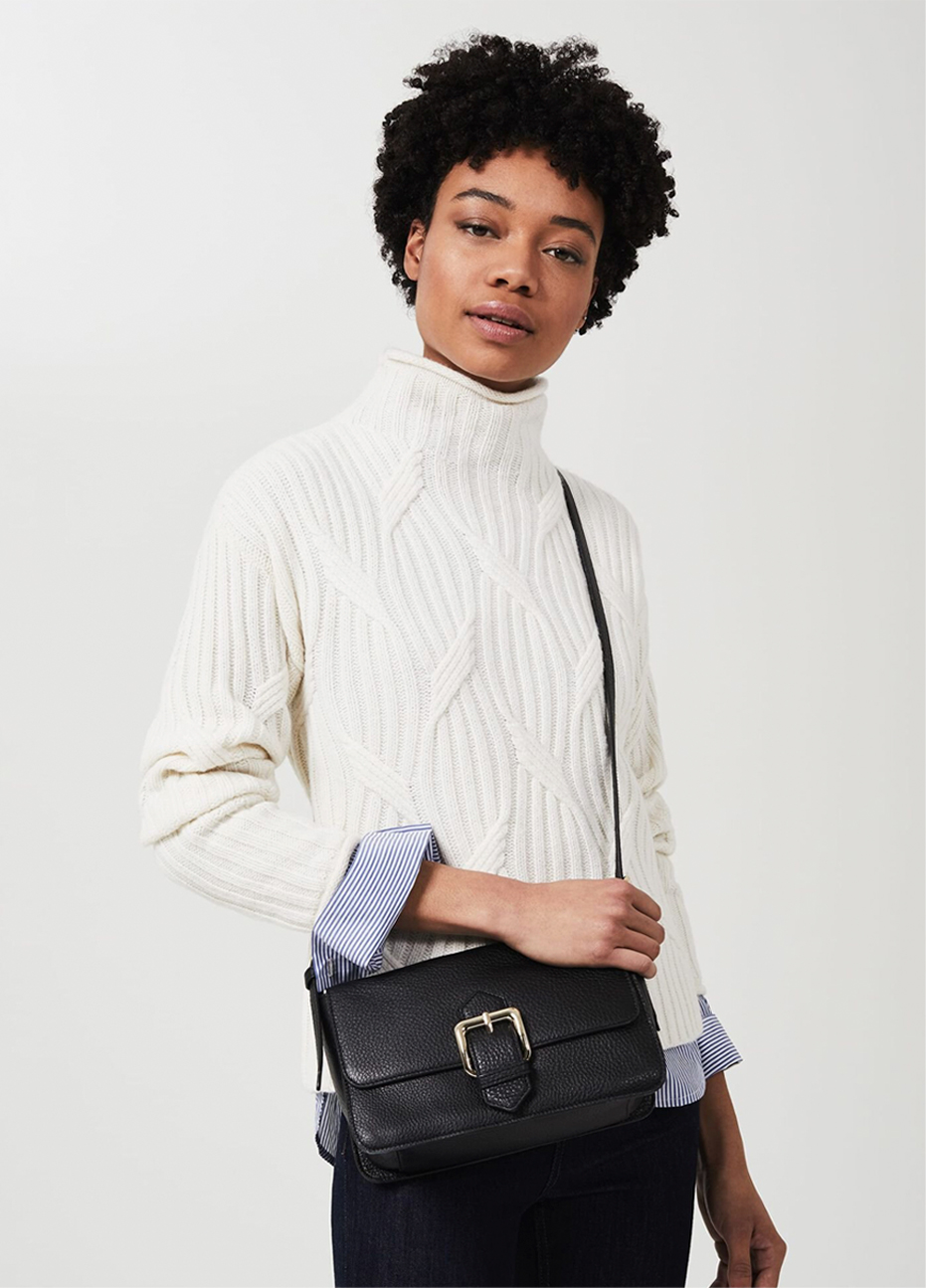 Image of model wearing a cream cable neck sweater layered over a pinstripe shirt.