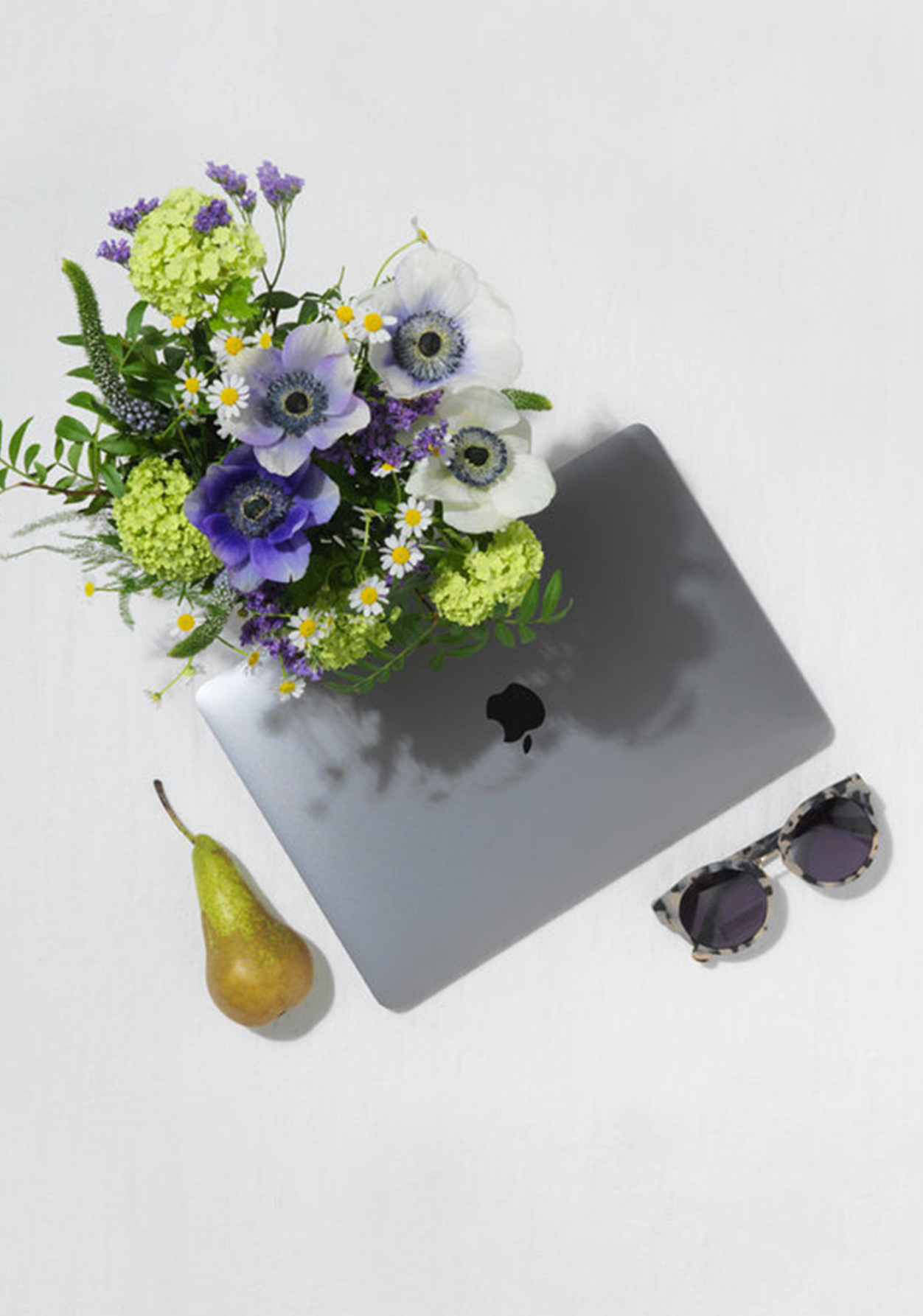 Flat Lay Of  A Laptop, Fuit, Flowers and Sunglasses
