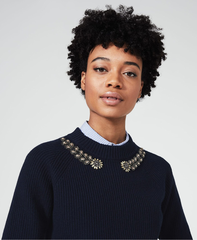 Model photographed wearing a navy jumper with embellished neckline.