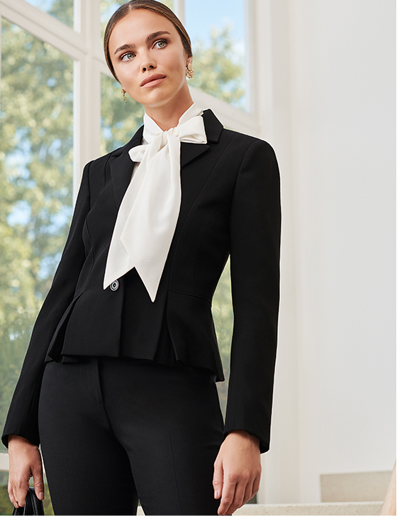 Model wears smart black suit and a white shirt