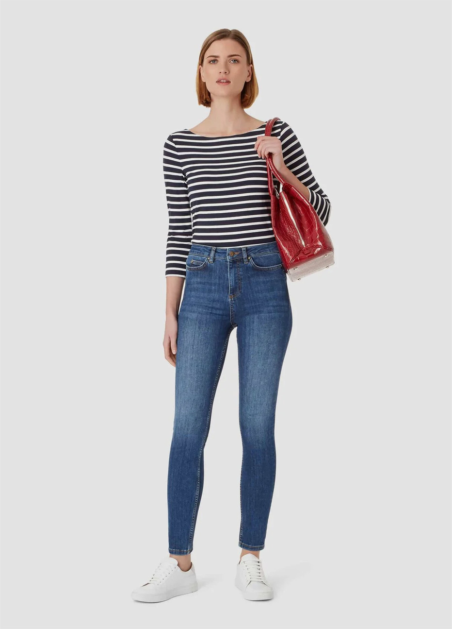 Striped top in black and white worn with blue jeans, white trainers and a red leather bag by Hobbs.