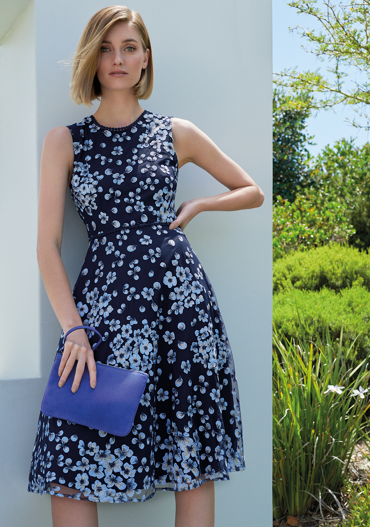 Floral occasion dress in dark blue with matching clutch by Hobbs.