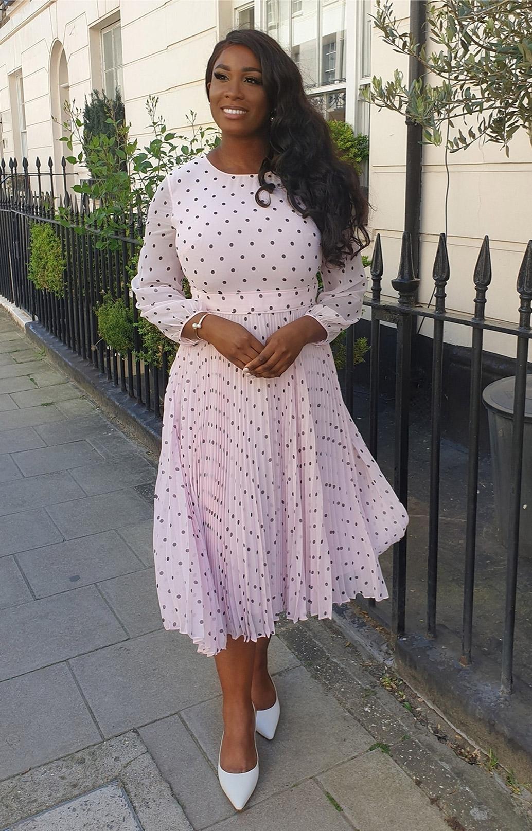 Fashion blogger @woman_ofelegance photographed at a cafe wearing Hobbs' Selena pink polka dot dress.