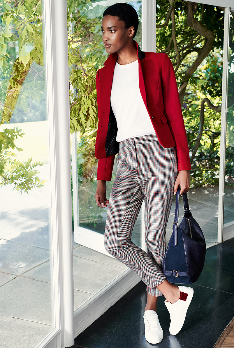 Full length image of model wearing a Hobbs red jacket over a white t-shirt with checked trousers.