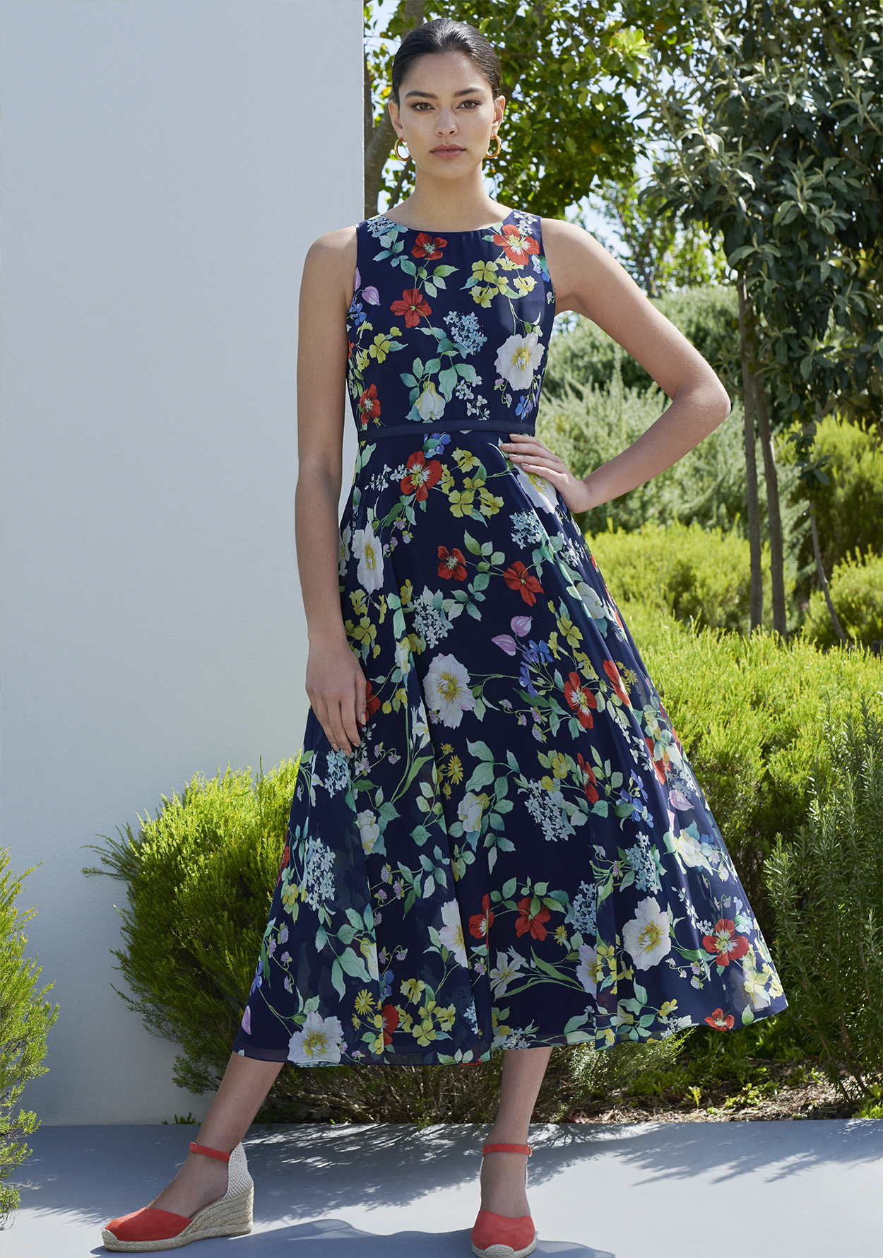Women poses in a dark blue floral midi dress with bright red espadrille heeled shoes.