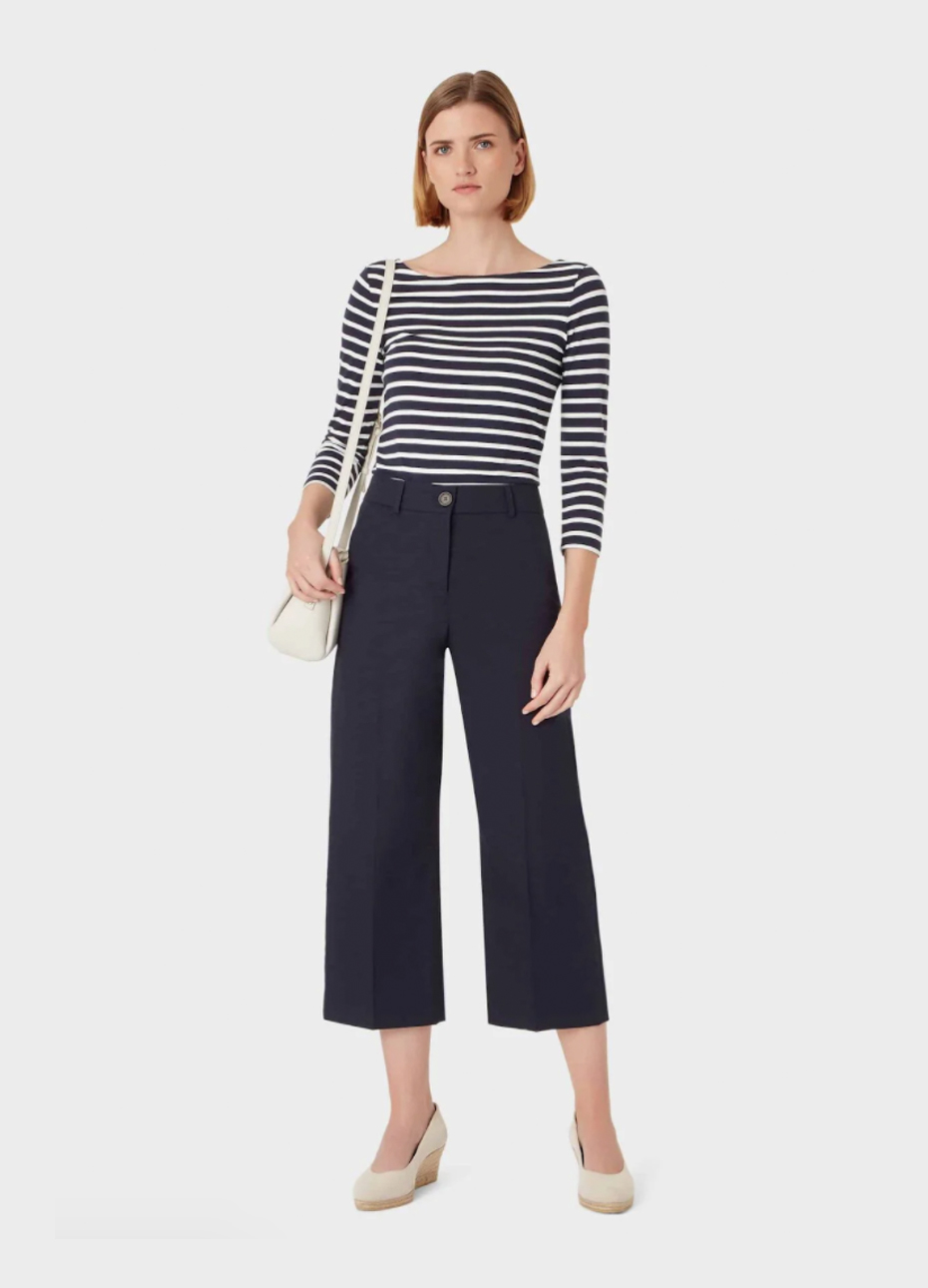 Mid-sleeve top with black and white stripes paired with black wide trousers for women, wedge espadrilles in nude and a white crossbody bag.