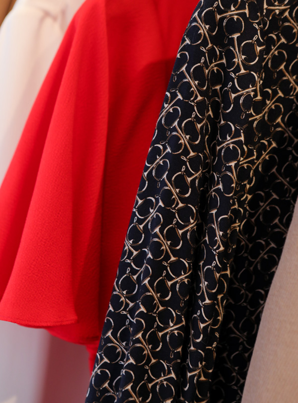 Interior shot of wardrobe with red, cream and patterned black clothing