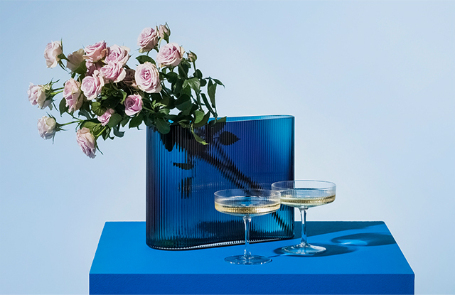 Spruce Up your fizz with two champagne coupes styles with a cobalt blye vase and dusky pale pink roses