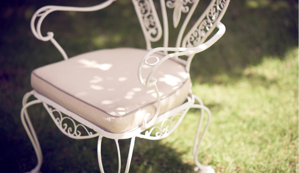 A white wrought iron chair with a pale pink cushion.