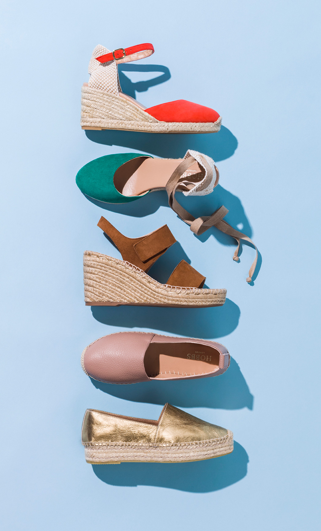 A variety of espadrille sandals lie, displayed on a pale blue background
