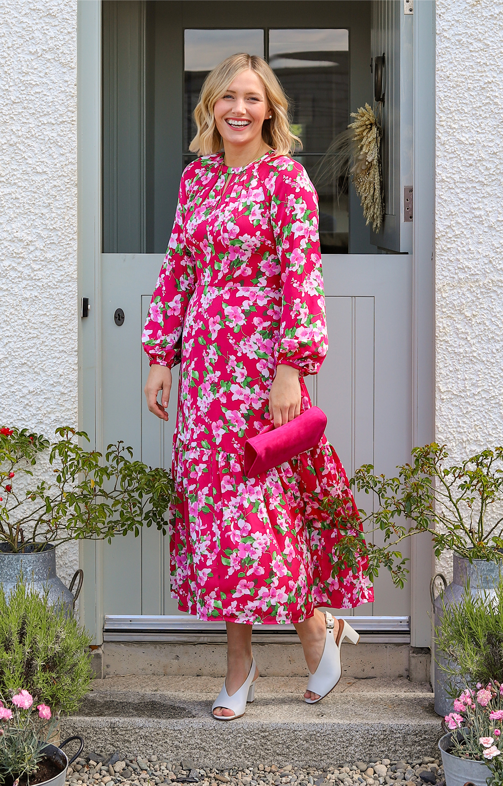 Lifestyle blogger @all.thats.pretty photographed in her garden wearing Hobbs' Marilyn pink floral midi dress with Kali ivory heels.