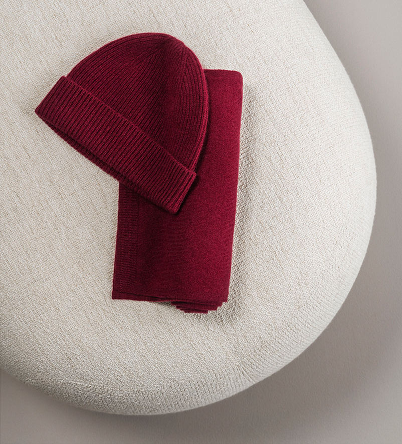 Burgundy cashmere knitted hat and matching scarf on a footstool.