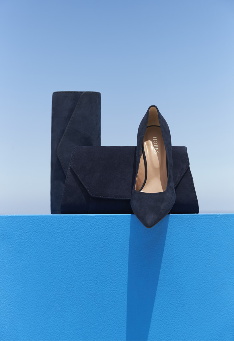 Grouping of matching navy blue accessories including two navy suede clutch bags alongside a classic navy pointed court shoe.