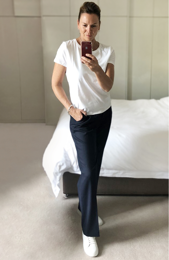 An outfit for relaxing - Sally wears a simple but stylish white t shirt and straight-leg trousers with white leather trainers.