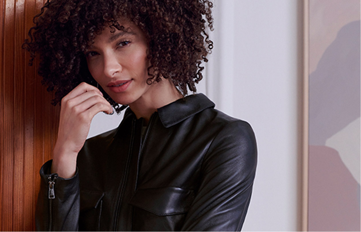 Model wears a leather jacket and belted linen trousers.