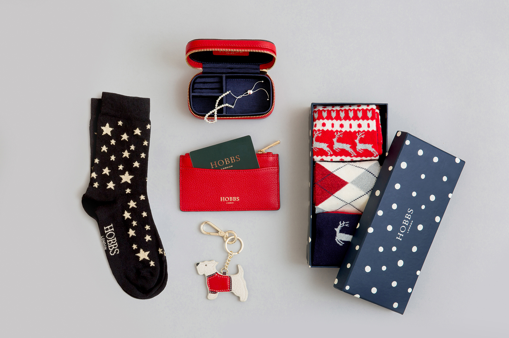 A selection of Christmas stocking fillers including a box of socks, keyring and leather cardholder.