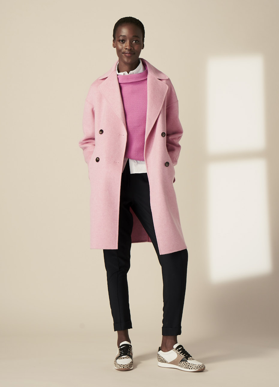 Hobbs model wearing a pink pea coat over a pink wool jumper and a white shirt, styled with black jeans and trainers.
