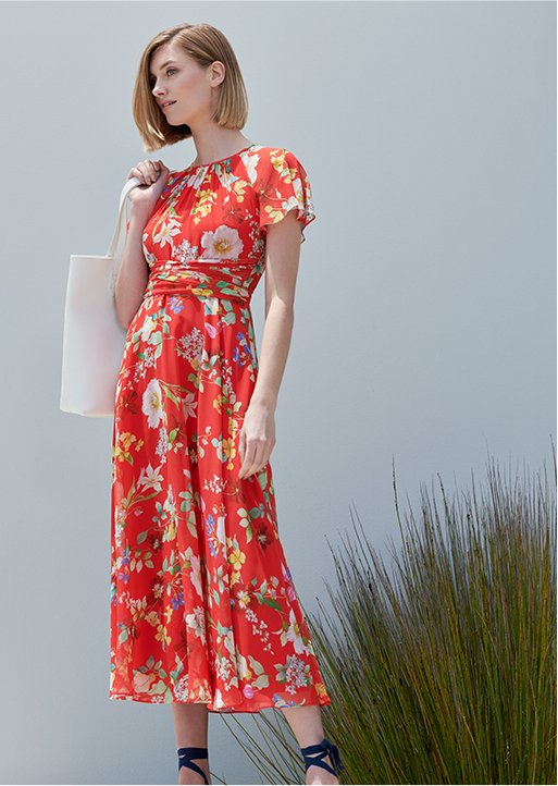 Woman stands in a red floral midi dress wearing navy blue espadrilles and holding a white leather tote bag