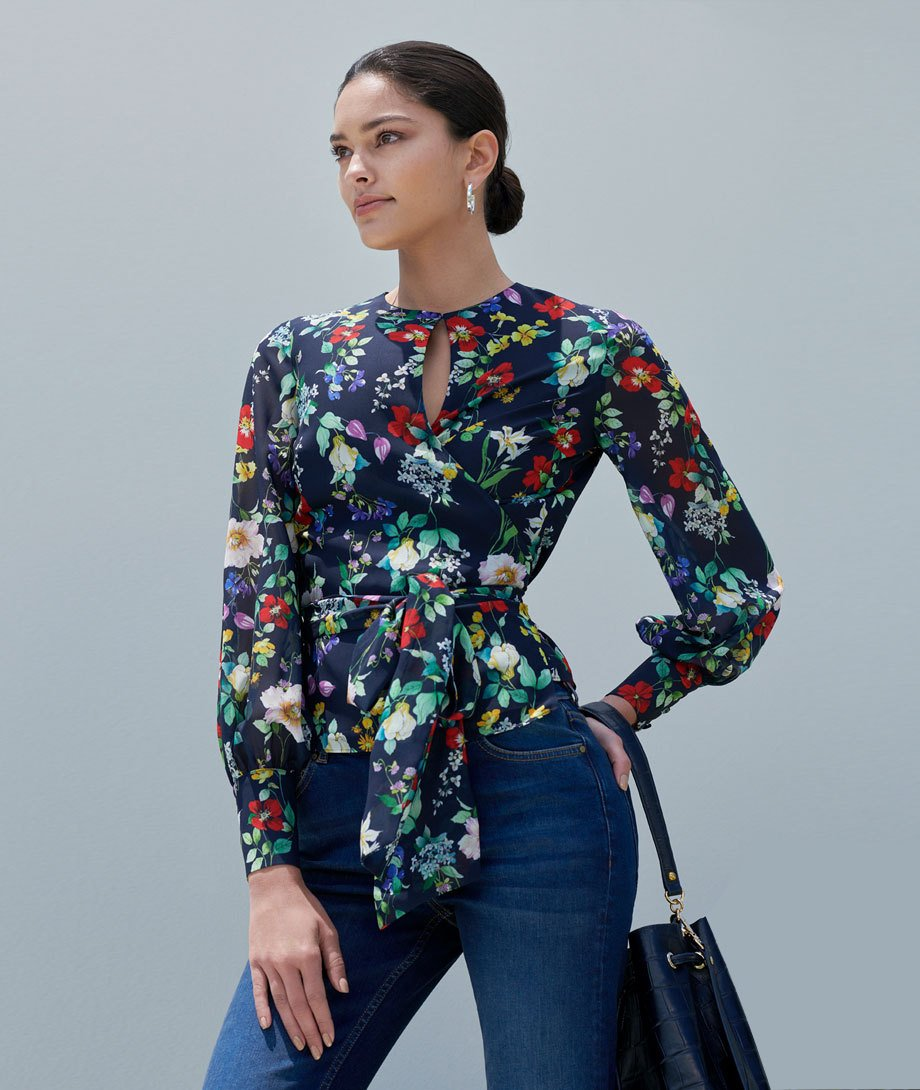 Floral wrap blouse with waist tie detail, worn with indigo blue jeans and a dark blue leather bucket bag, by Hobbs.