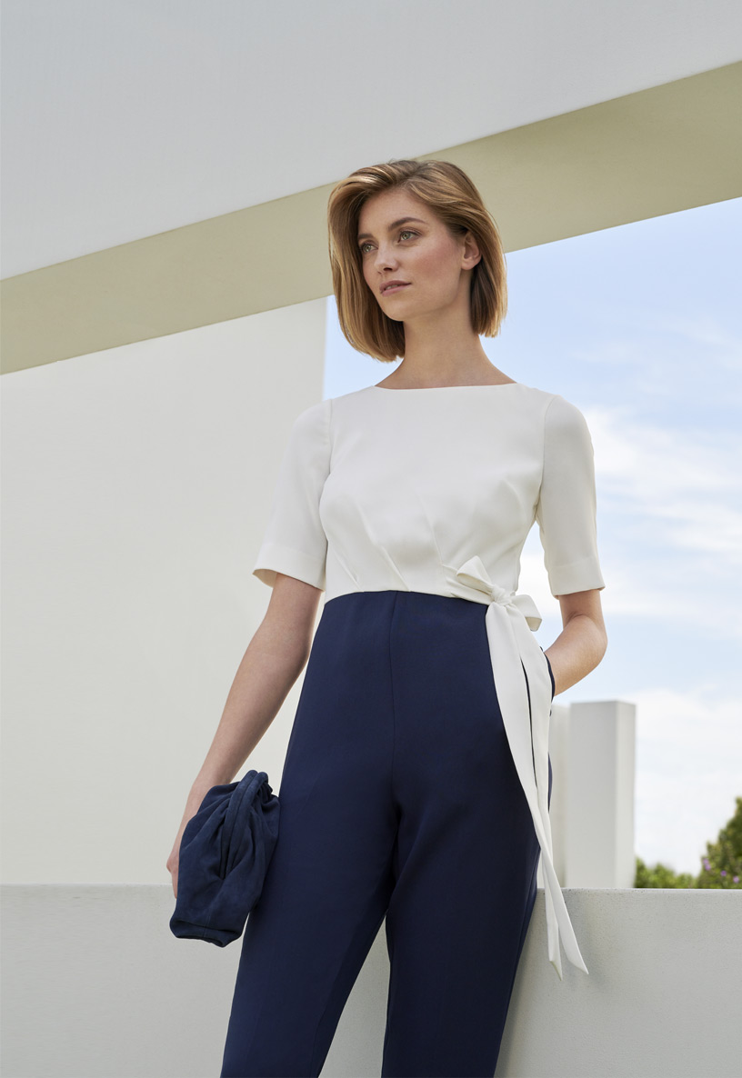 Blonde woman model in a white and navy jumpsuit with a navy blue suede puch style clutch bag.