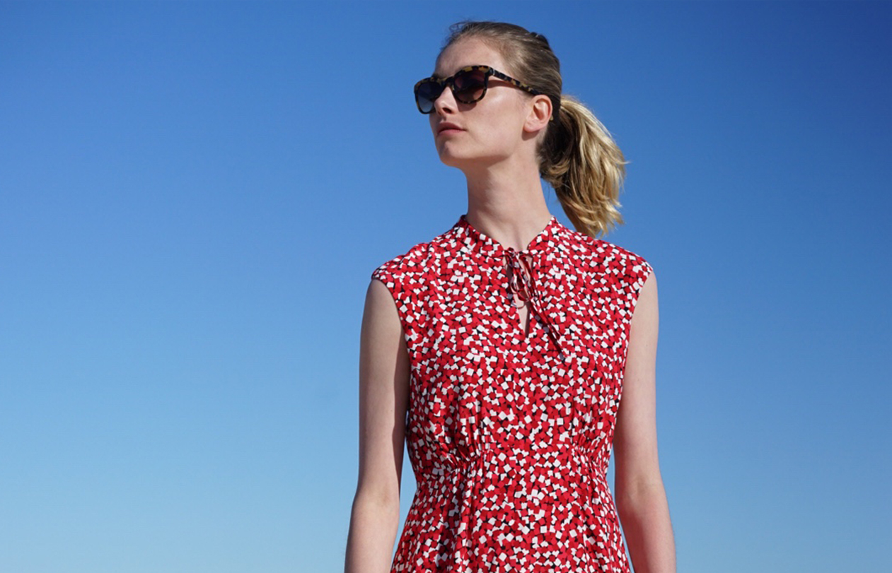 A Hobbs model wears a red dress with short cap sleeves and a neck fastening at the front, styled with sunglasses with blue sky in the background.