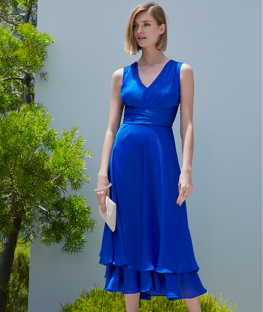 Midi length fit and flare dress in blue with a white clutch by Hobbs.