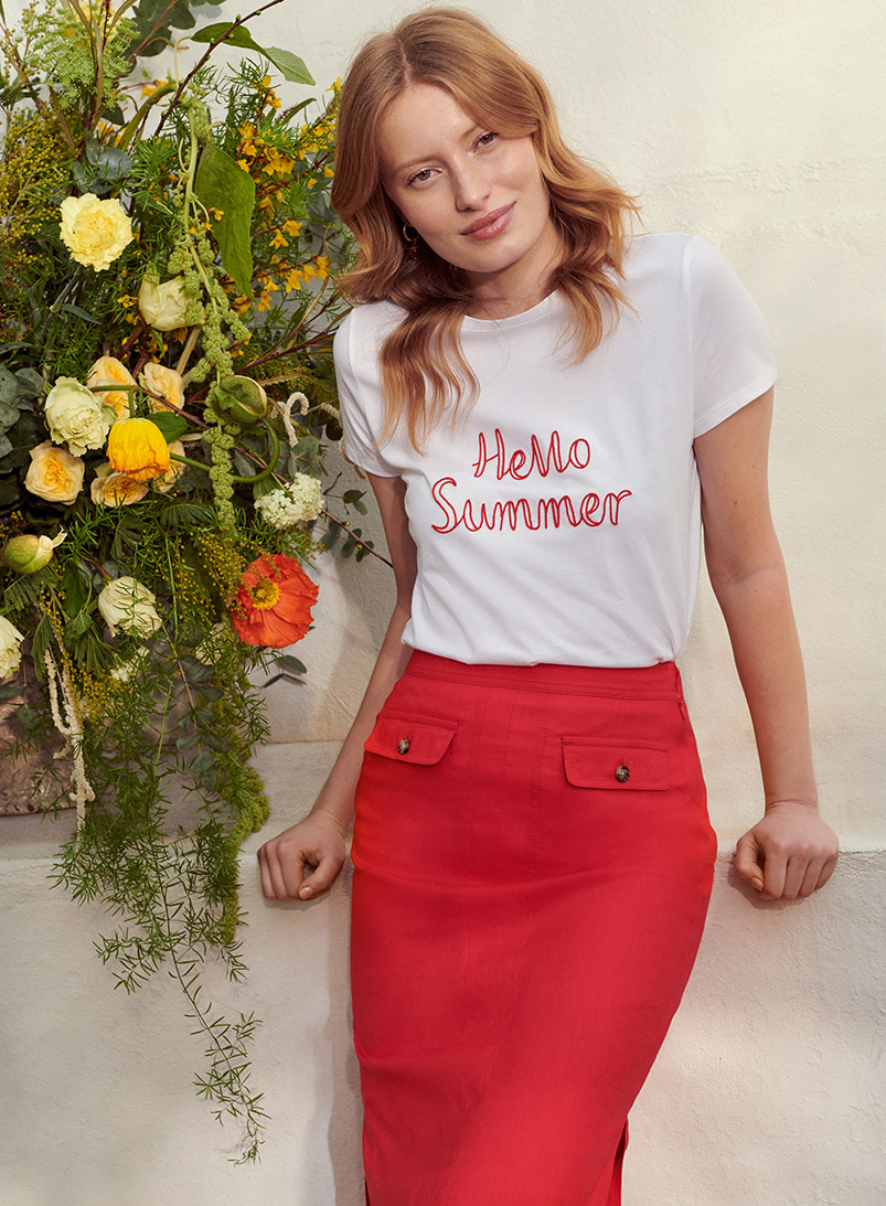 Model wearing a Hobbs t-shirt with 'Hello Summer' slogan in a garden.