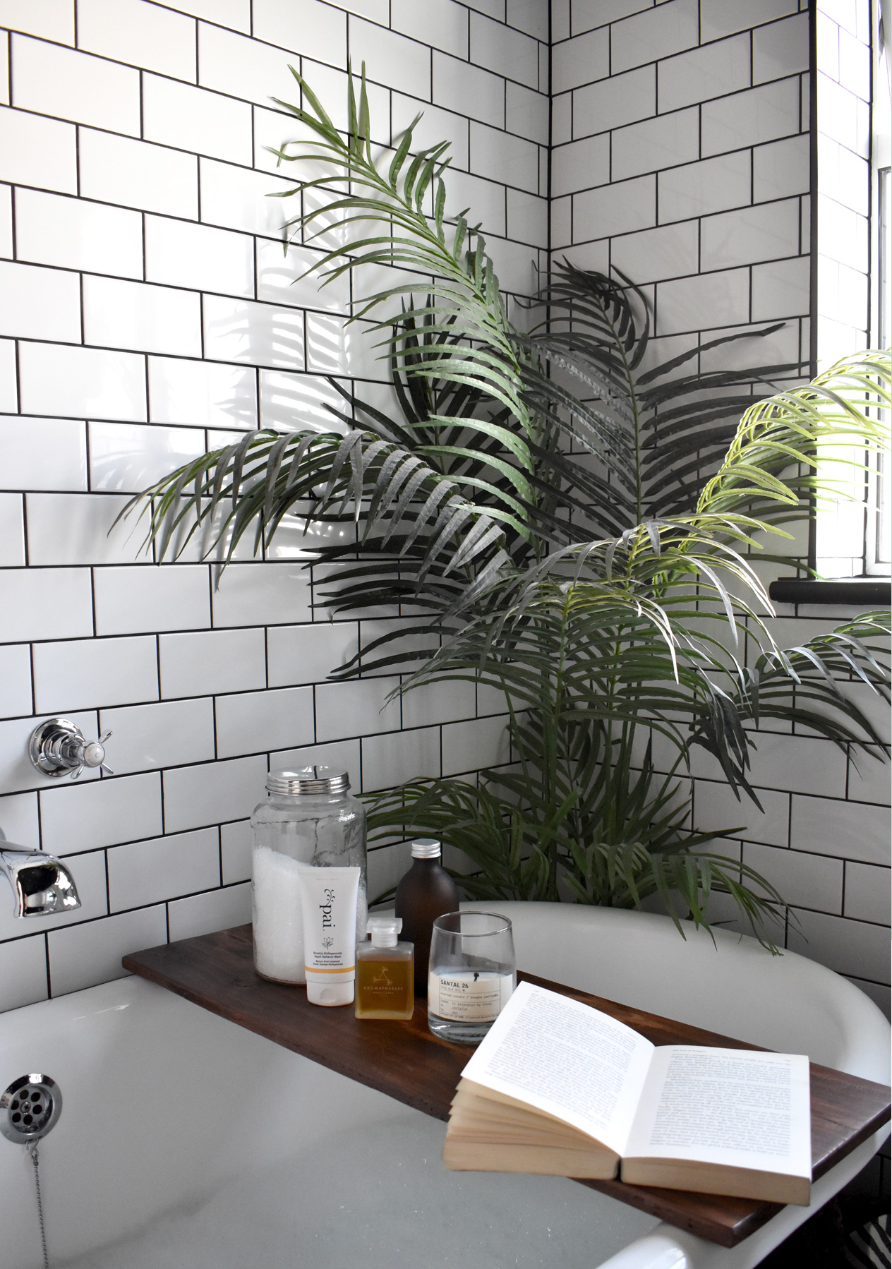 A serene white bathroom with white metro tiles and black grout, a green leafy plan and an array of luxurious bath products.