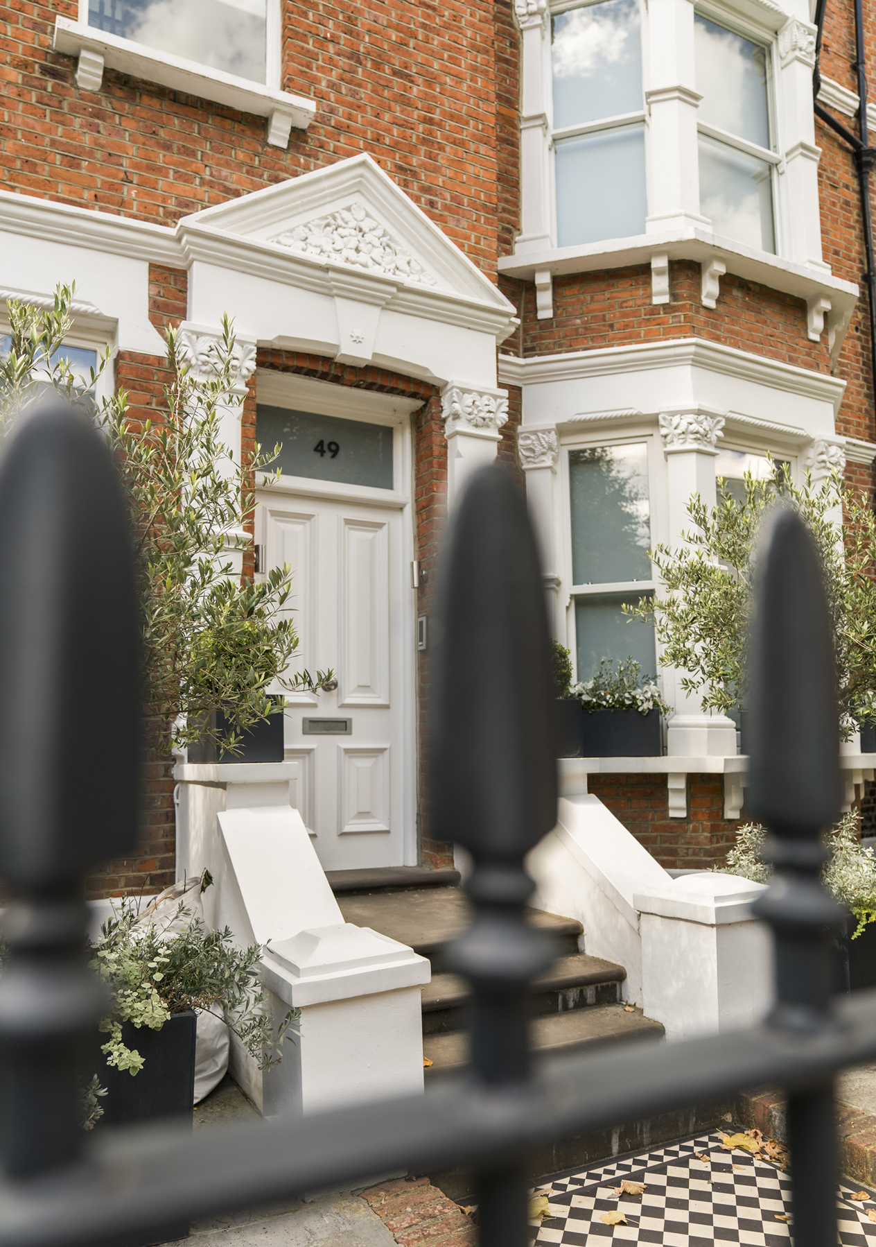 A red brick Edwardian house with a white front foor with a black and white tiled stairs