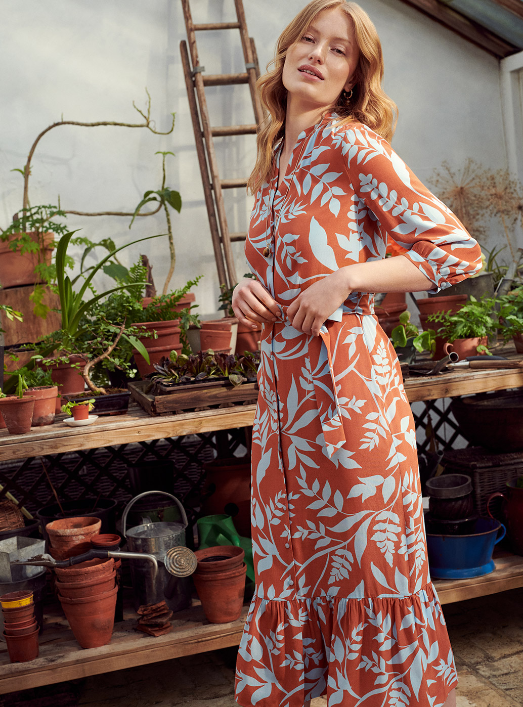 Model wearing a printed shirt dress stands beside potted plants.