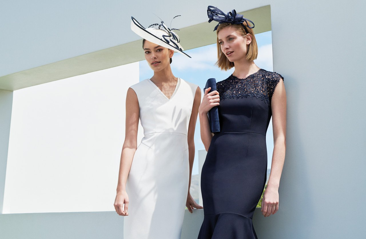 Two Women Pose in Ivory and Navy Event Dresses Wearing Fascinators