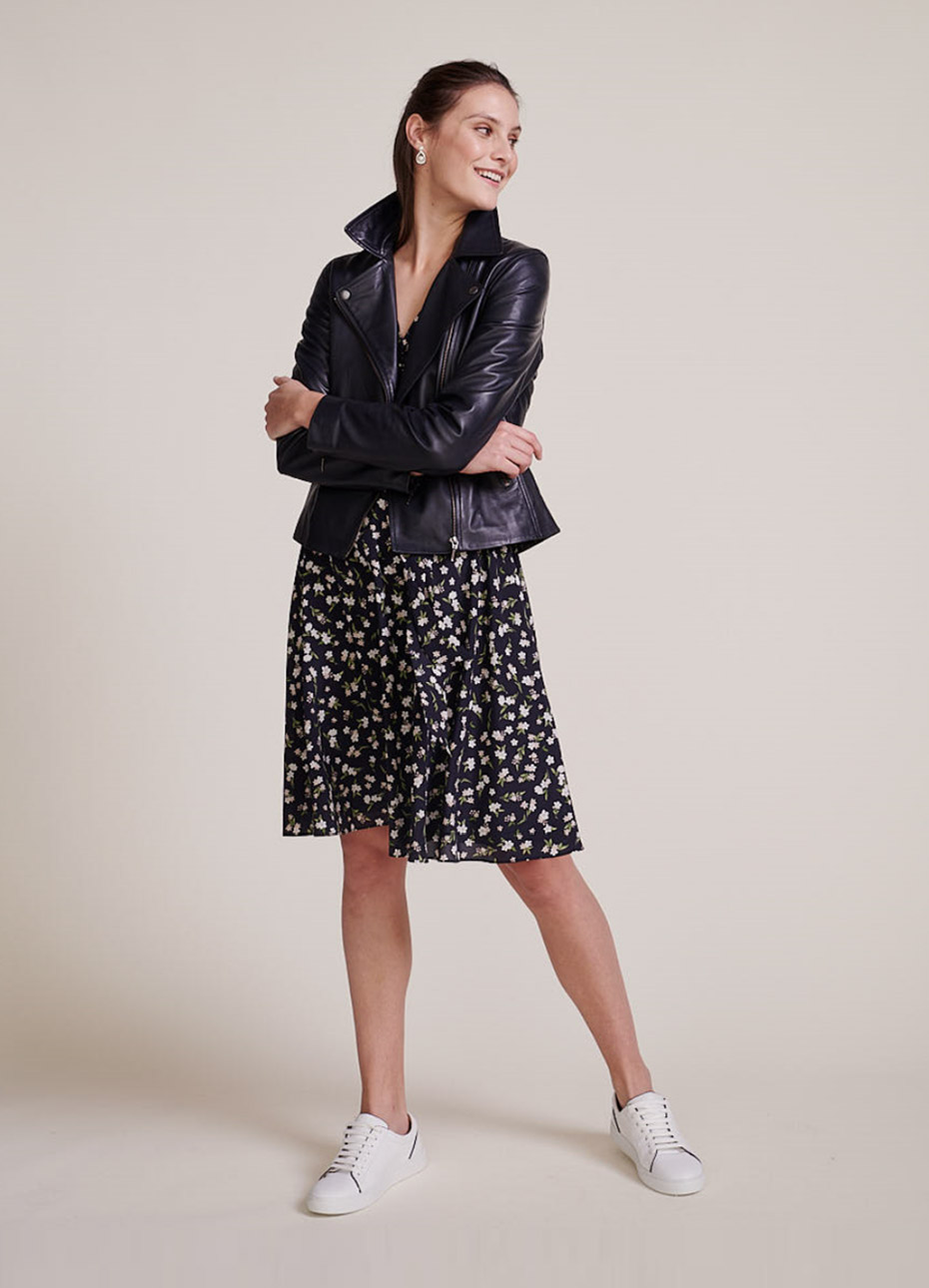 Hobbs model wearing a black leather jacket over a floral dress with white trainers.