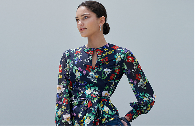 Model poses in the nevy blue floral wrap meadow blouse top