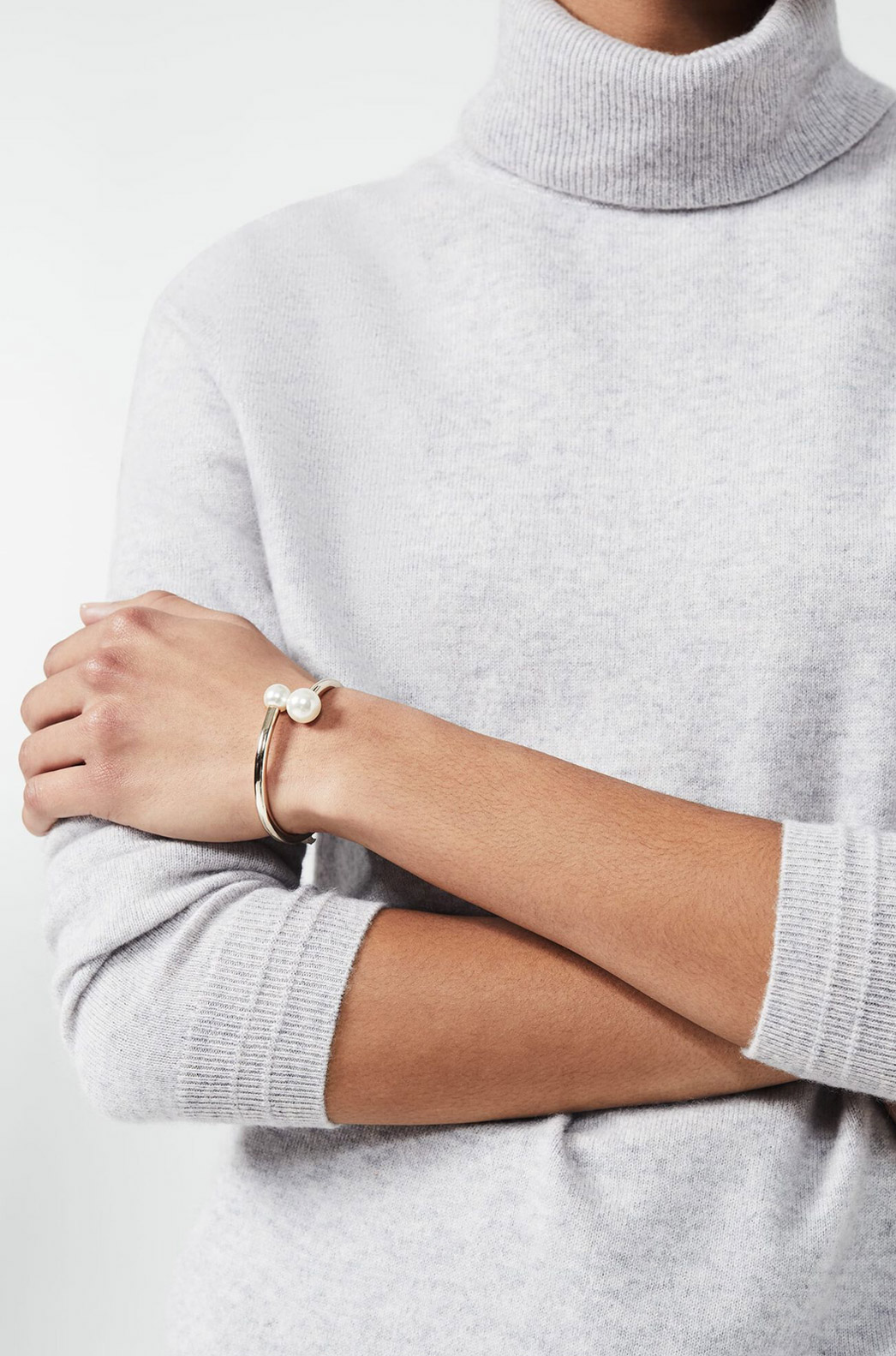 Model photographed wearing a grey jumper with a gold pearl embellished cuff.