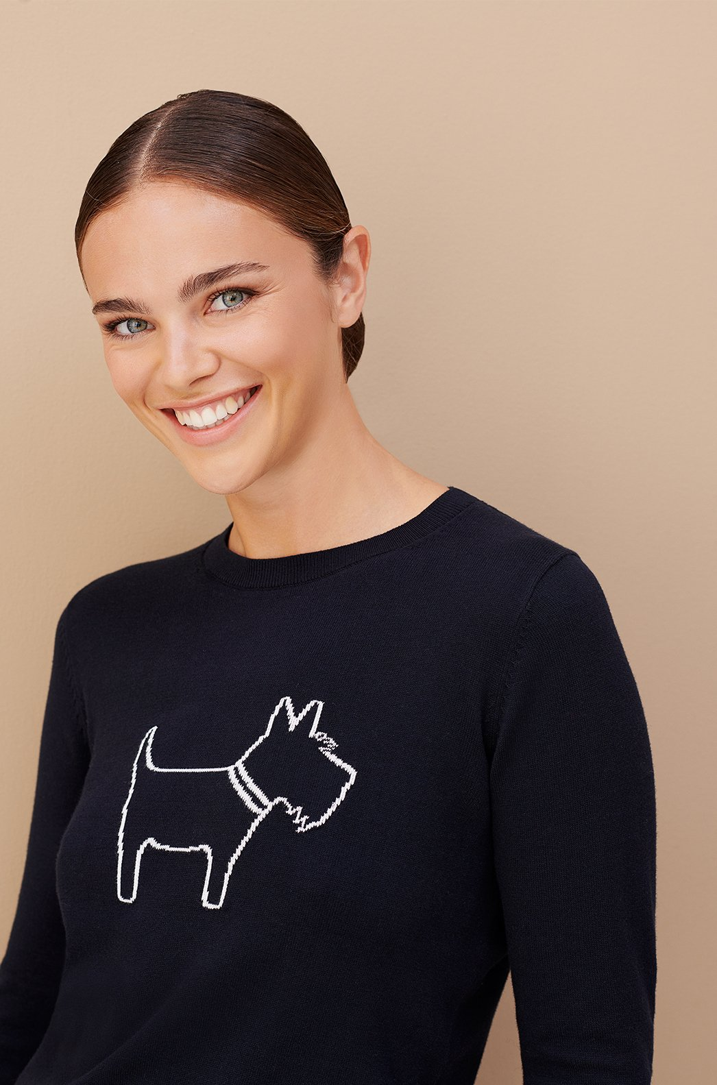 Model wears a novelty jumper featuring a dog from Hobbs.