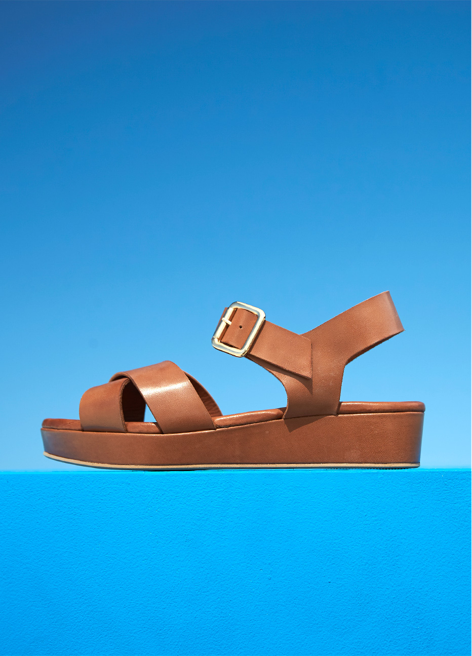 rown leather flatform sandal from Hobbs set against a blue background.