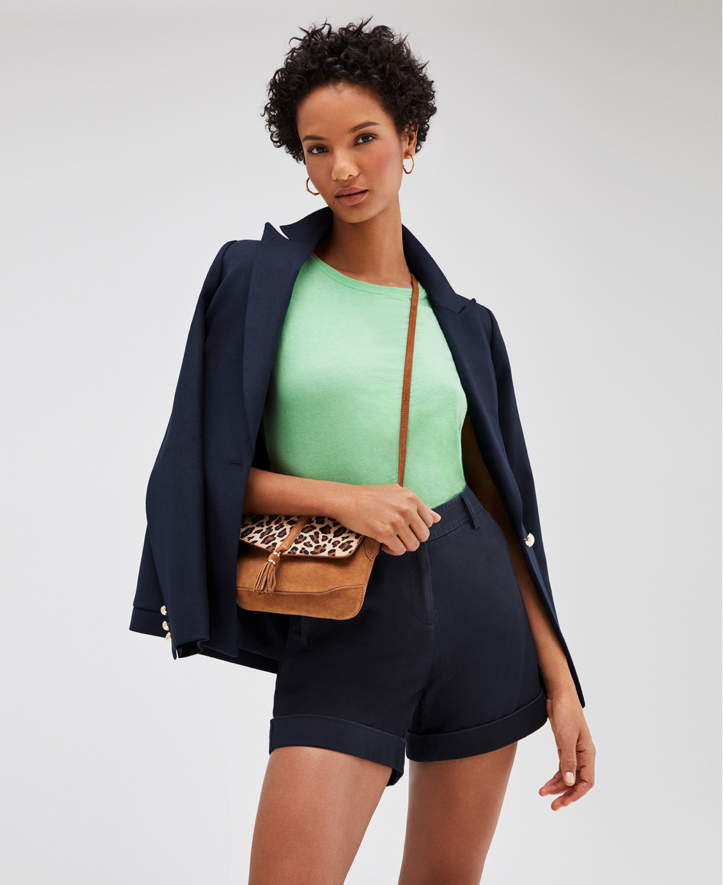 Model wears a navy blue jacket, green tshirt with navy blue shorts and a brown and leopard print cross body bag