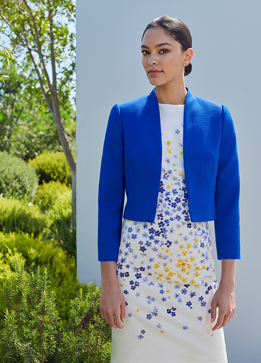 Woman poses in white formal shift dress witha blue and yellow floral pattern with a matching cobalt blue jacket